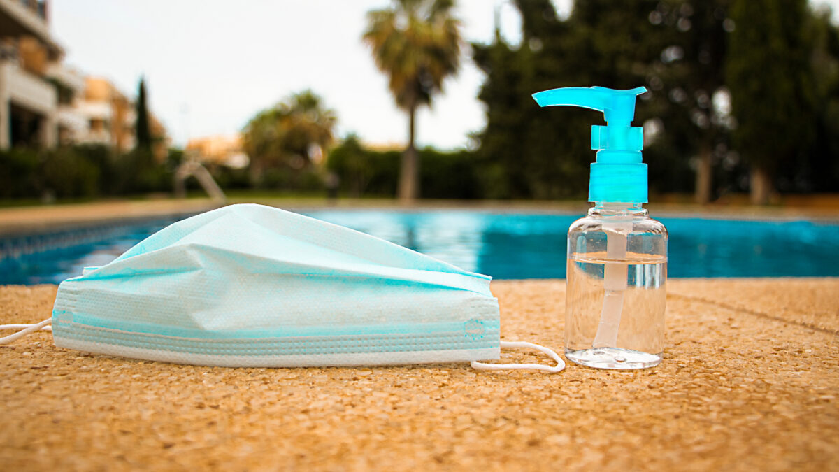COVID-19 hand sanitizer and mask by a pool
