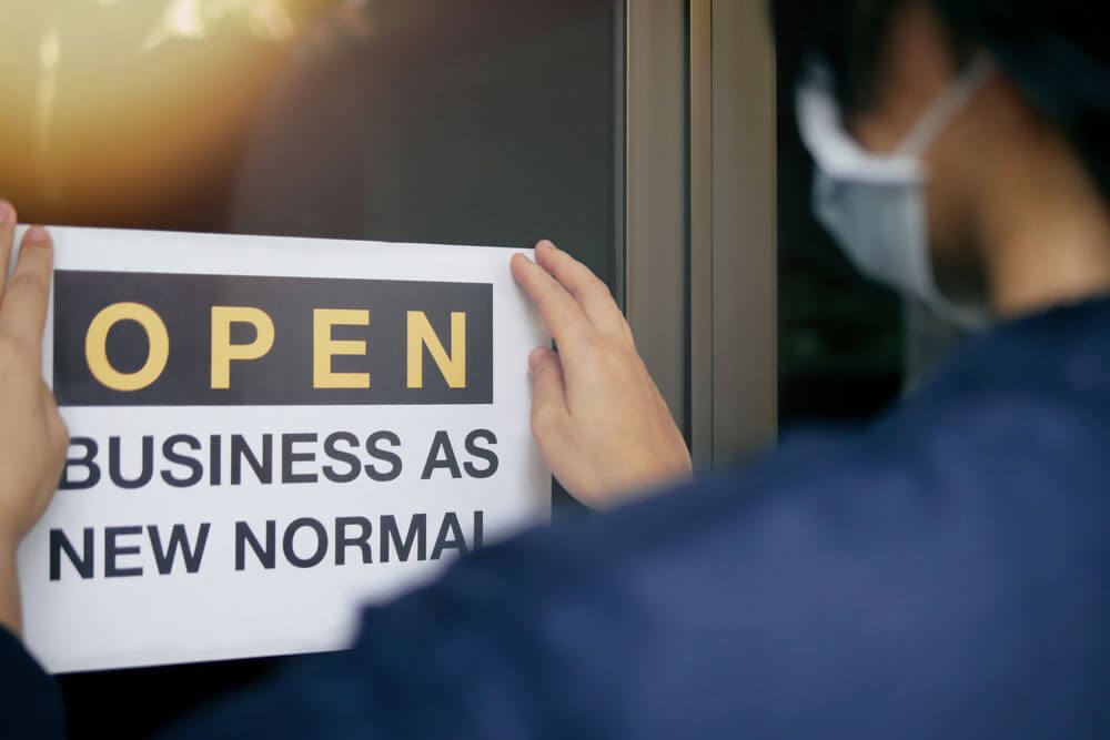 "The Budd Group open sign that reads, ""Open: Business as New Normal"""