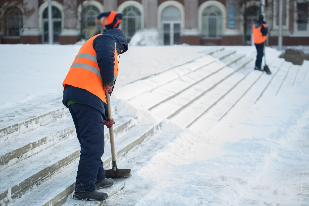 Workers shoveling snow off steps