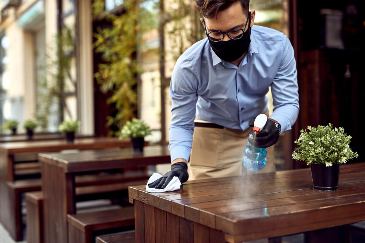 Waiter disinfecting a table at a restaurant